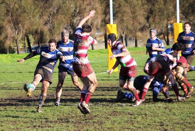 Taroona Penguins scrum-half Andrew Wicks' clearing kick eludes Eastern Suburbs defenders at Rugby Park in Hobart.