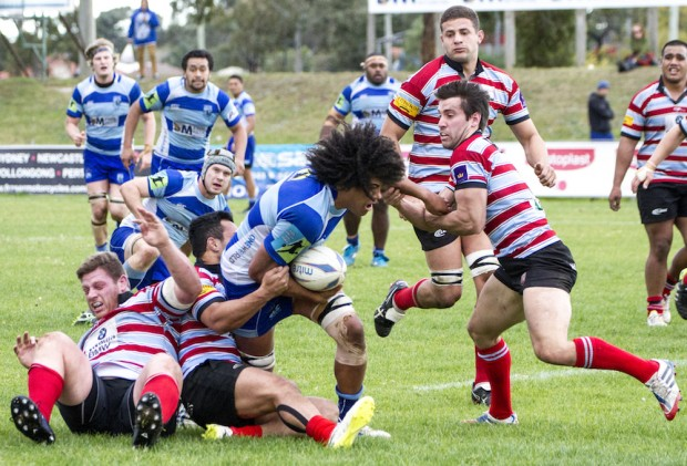 Parramatta flanker Josh Kaifa crashes into some Souths defenders _photo by Pat Dunne