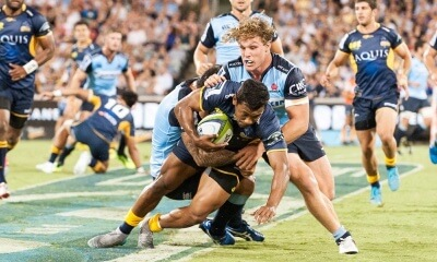 The Brumbies' fullback, Aidan Toua is tackled by the Waratahs' captain, Michael Hooper.