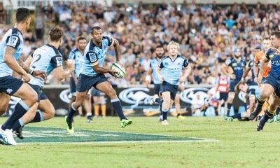 Kurtley Beale passes the ball along the Waratahs' line.