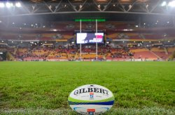 Stock Photo. Gilbert Super Rugby ball on grass with goal-posts and stadium lights