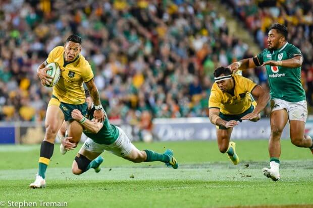 Israel Folau struggles to beat a tackle as Kurtley Beale hits the deck